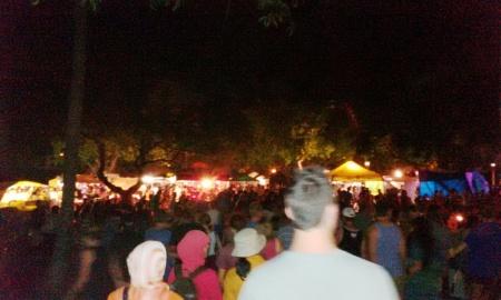 Penonton kembali mengunjungi stand-stand setelah menyaksikan kembang api penutupan di pantai